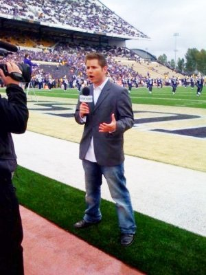 A sportscaster reporting on the sidelines of a football game.